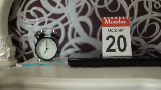 Woman`s hand overturns a calendar sheet.Desktop calendar and alarm clock is on the  table.