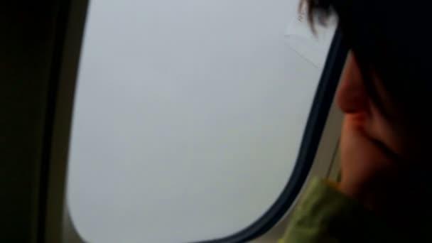 Mladá žena při pohledu přes okno v letadle