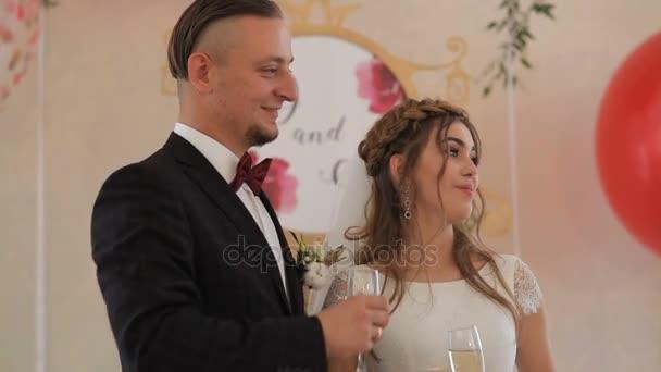 Novomanželé řinčí poháry s hosty