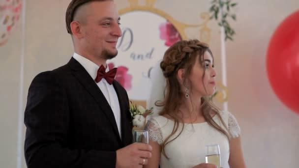 Novomanželé drží pohárky se šampaňským v ruce