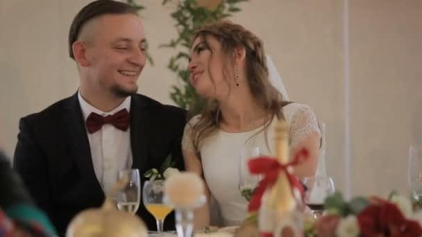 Novomanželé sedí u svátečního stolu a směje se