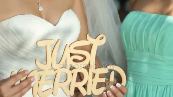 Šťastná nevěsta a ženich drží dřevěné cedulky Just se oženil na pozadí dřevěné zdi s pivoňky. svatební den
