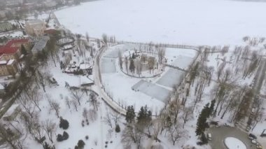beautiful view from the air to the winter city, park and frozen lake. Children skate, people relax in the fresh air. Winter family fun.