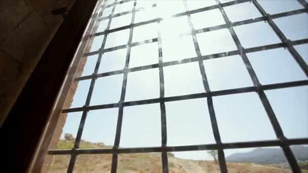 Pohled na hory oknem s roštem
