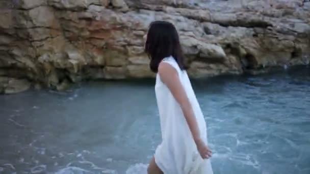krásná dívka v bílých šatech na břehu moře se těší na moře. Řecko