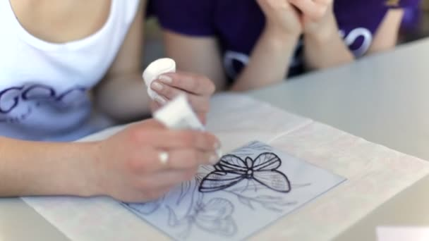 woman drawing butterfly with enamel on glass, close-up