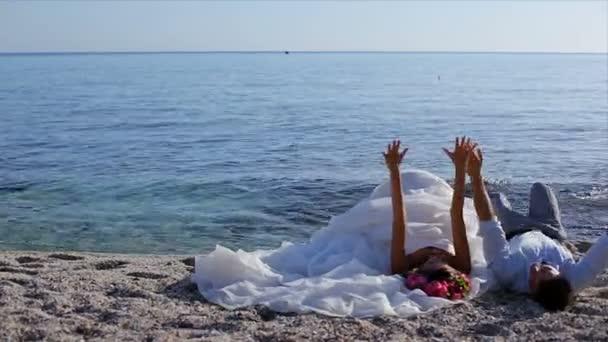 loving couple of honeymooners lying on beach, Greece