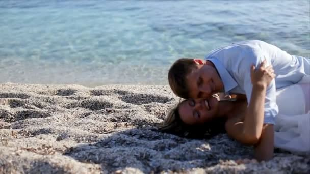 loving couple of honeymooners lying and embracing on beach,  Greece