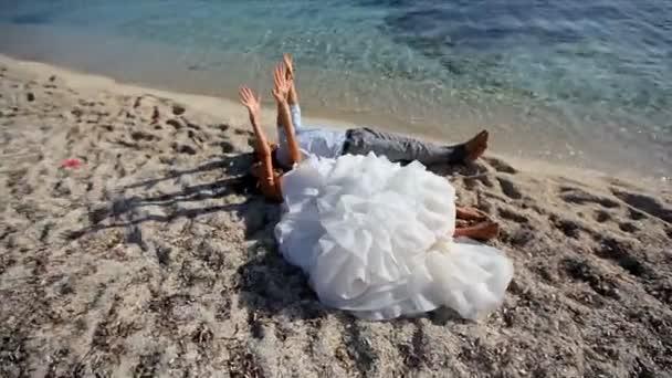 loving couple of honeymooners lying and enjoying on beach, Greece