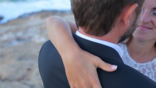 Nevěsta a ženich mazlení a líbání stoje na beach Řecko, svatební den koncept