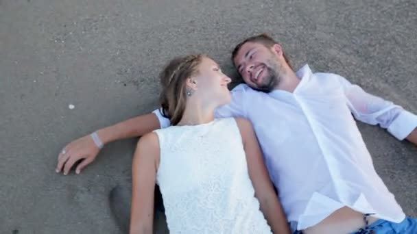 bride and groom lying on sandy beach and kissing, wedding day concept