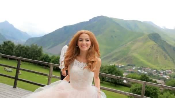 Svatební den. Šťastní novomanželé bavit na pozadí hor.