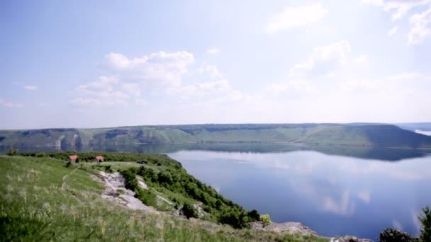 gyönyörű panoráma táj zöld dombok és egy széles folyó a felhők tükröződnek benne. Légi felvétel