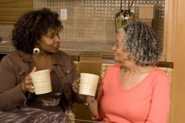 Senior woman having coffee with her daughter.