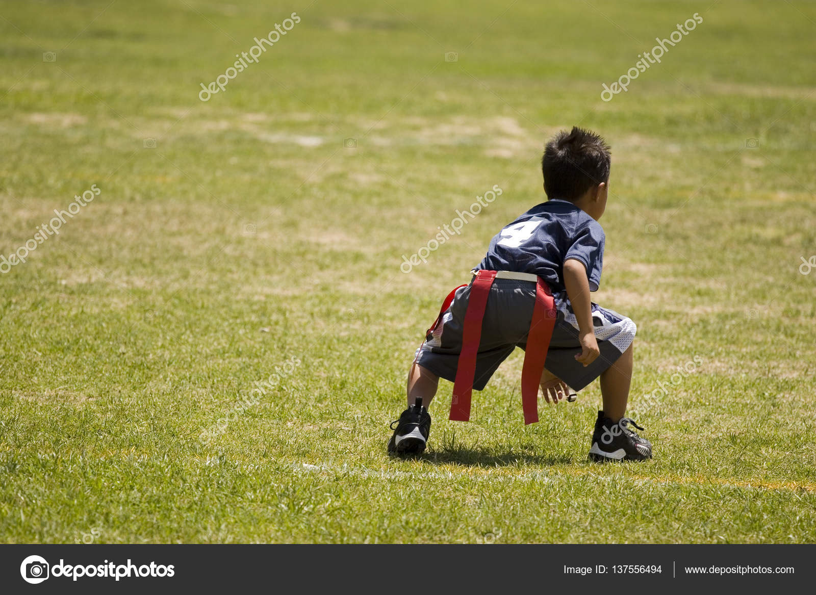 Little boy kid playing flag football on an open field ...