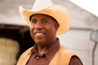 African American cowboy smiling and laughing.