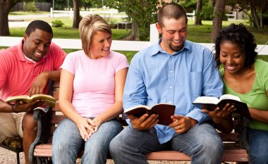 Diverse group of people talking and reading.