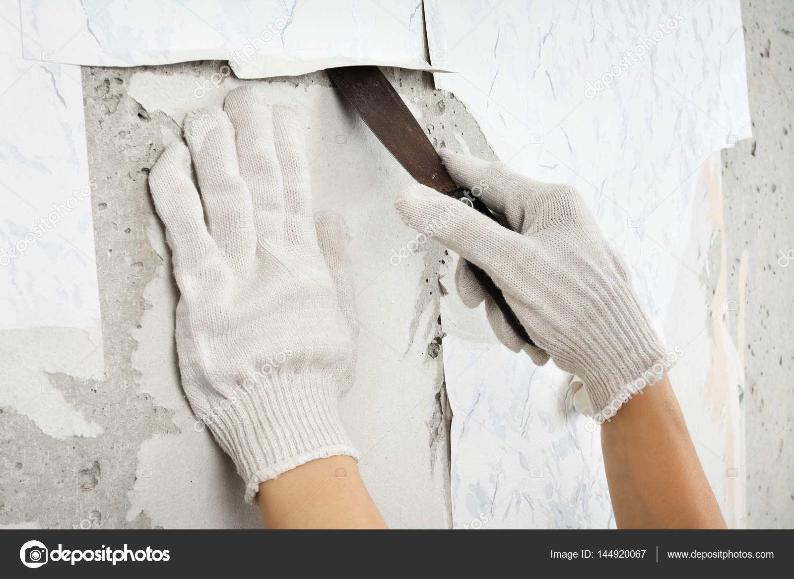 Hands In Gloves Removing Old Wallpaper With Spatula Stock Photo