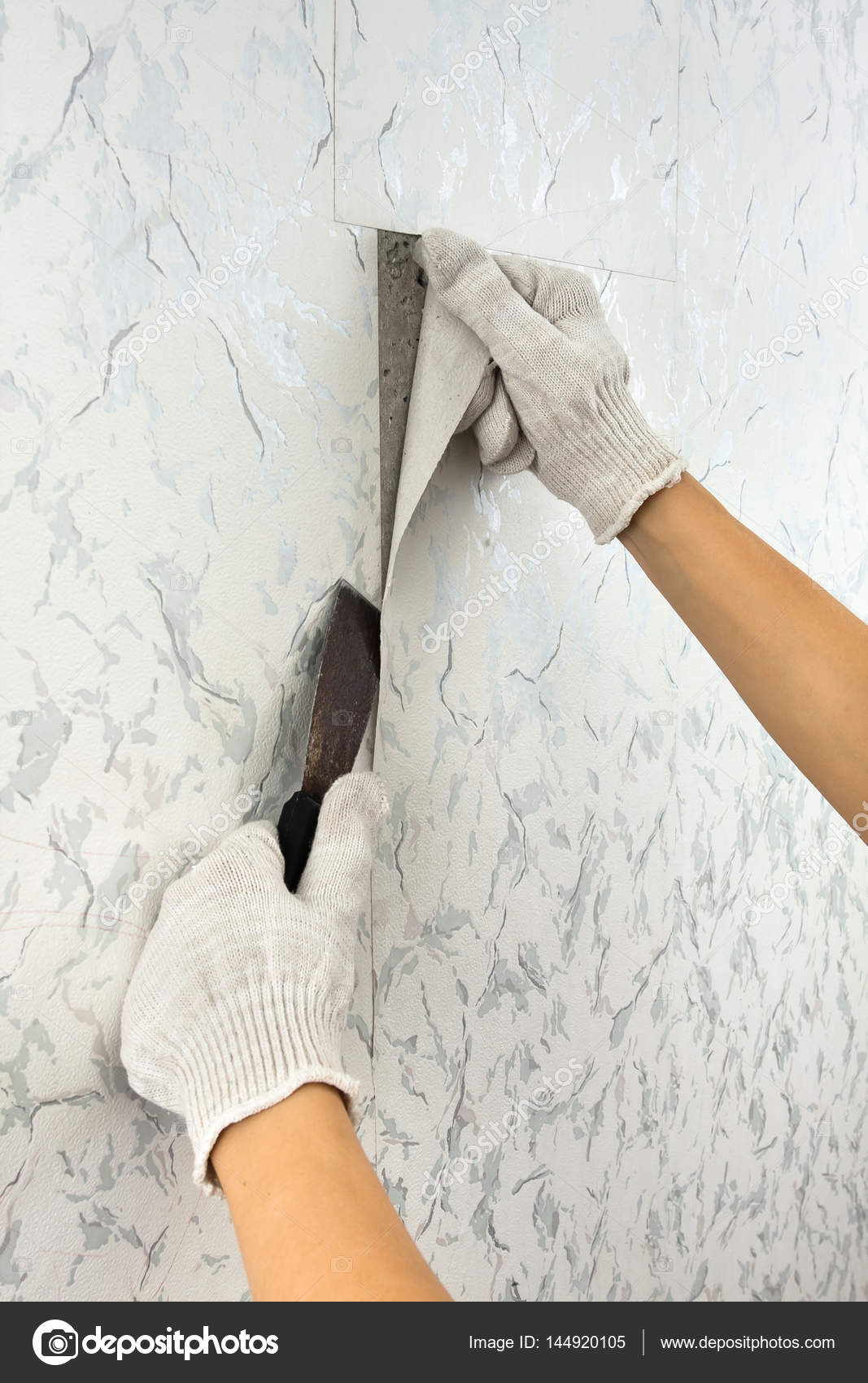 Hands Removing Old Wallpaper With Spatula Stock Photo