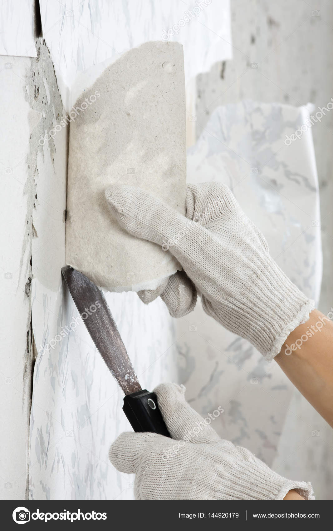 Hand Removing Old Wallpaper From Wall With Spatula Stock Photo