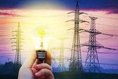 Energia elettrica - mano che tiene una brillante protezione ambientale lampadina - concetto di spese e risparmio di energia-