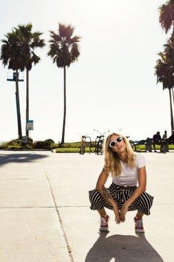 fashionista girl squatting on the broadwalk.