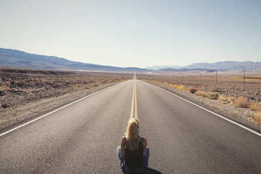 woman sitting alone on street in the middle of nowhere. wanderlust concept