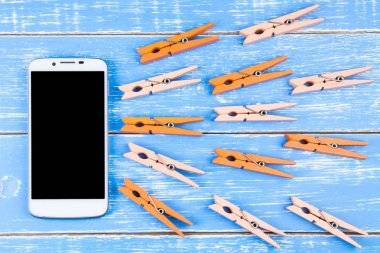 Orange wooden pegs on blue wooden background with smartphone and