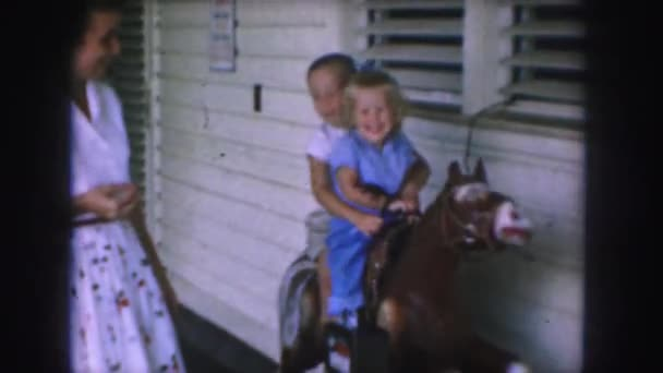 kids riding on wooden horse toy