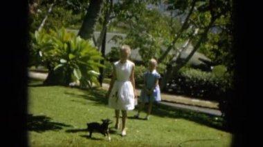 girls with dog walking in garden