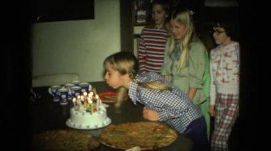 dívka s copánky foukání narozeninové svíčky na dort