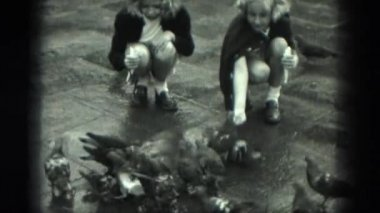 girls in city feeding pigeons
