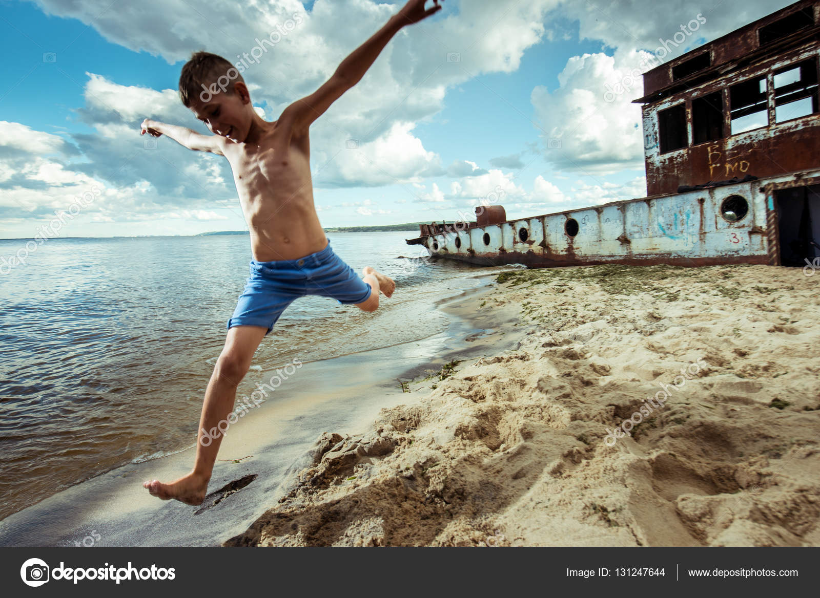 d2c82be1e Boy shorts is happy jumps and flips on the beach in summer– stock image