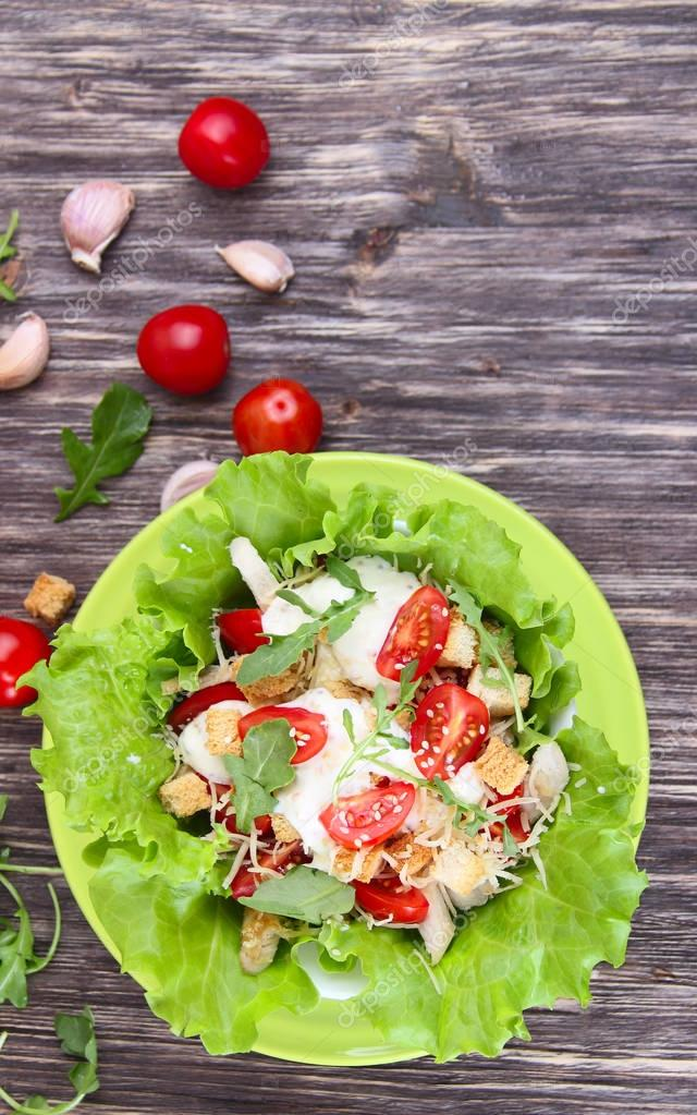 Caesar salad and fresh tomatoes on a wooden table