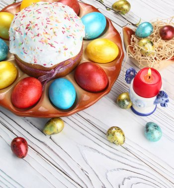 Easter bread and colorful eggs on a wooden, white background. Easter background.