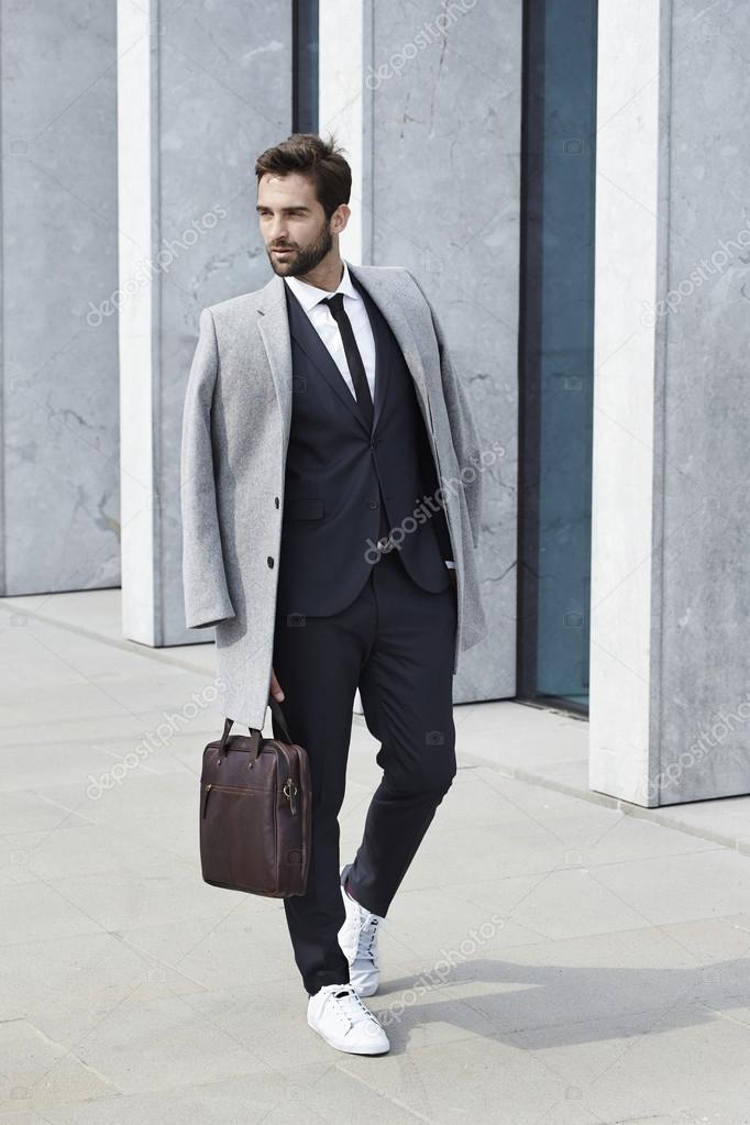 Portrait of handsome suited businessman with coat and briefcase, looking away