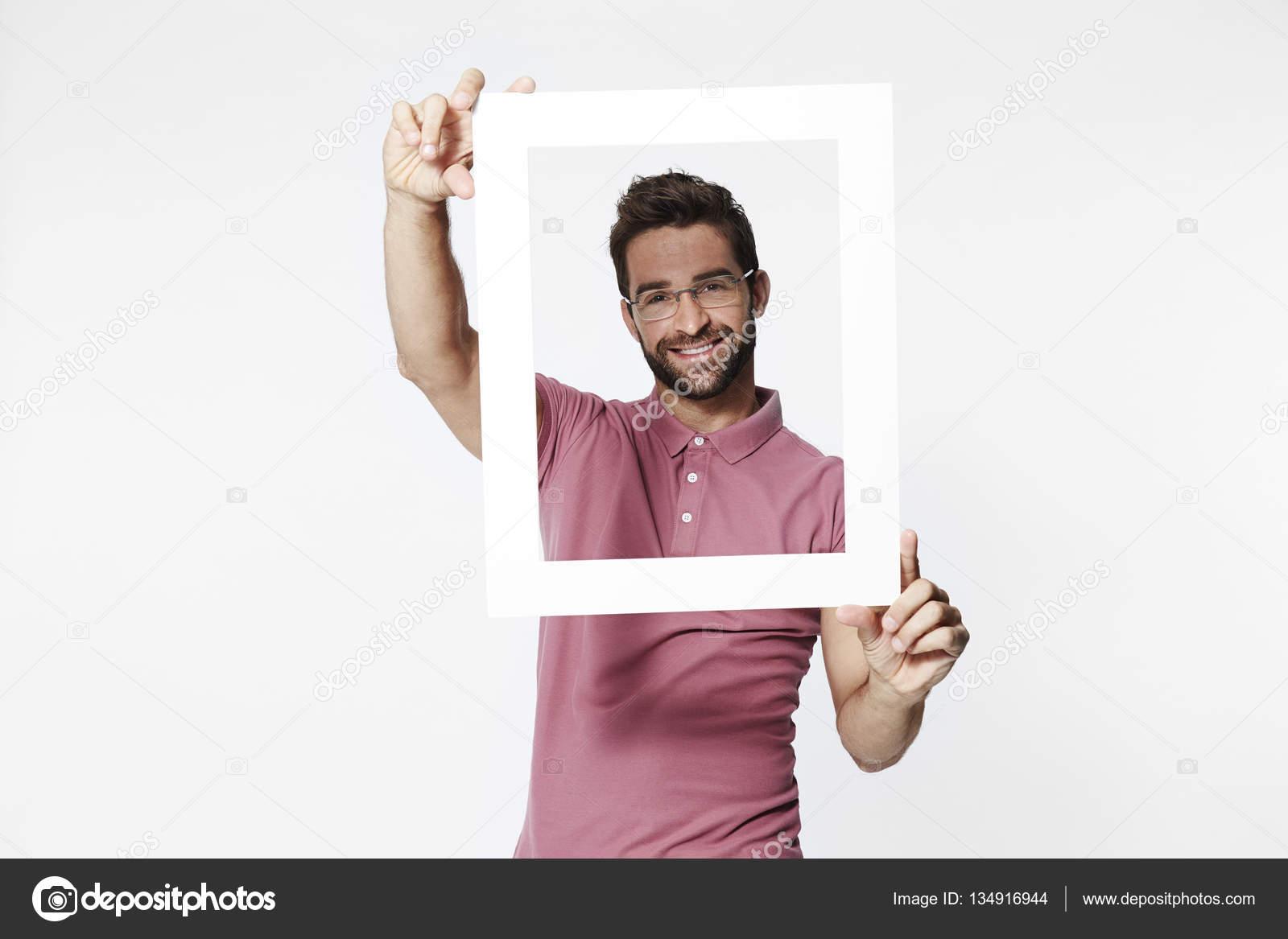 Smiling man holding frame — Stock Photo © sanneberg #134916944