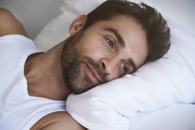 Man waking up in bed