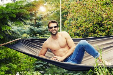 Shirtless man in hammock