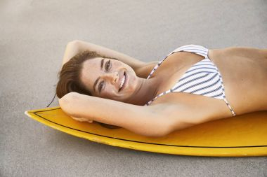 Surfer girl lying on board