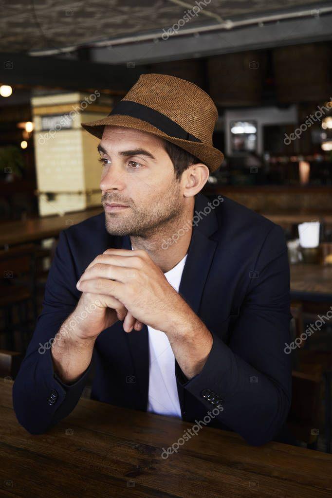 Guy wearing hat in cafe, looking away