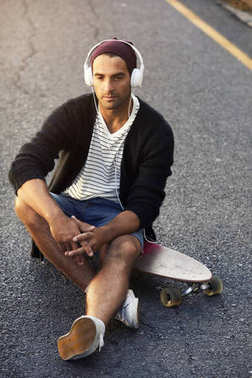 Young man sitting on skateboard wearing headphones