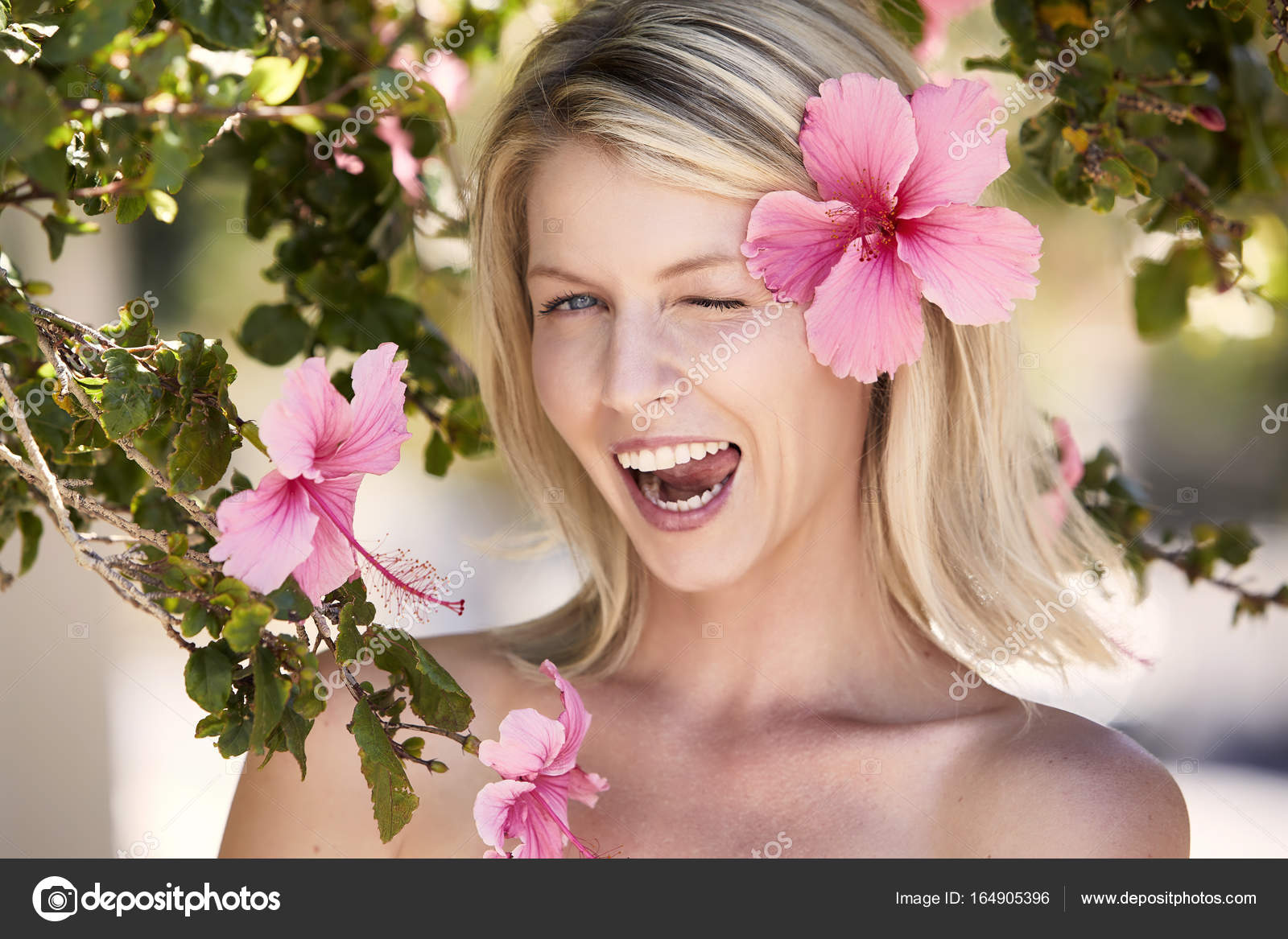 Beautiful woman with flower in hair stock photo sanneberg 164905396 beautiful woman with flower in hair winking at camera photo by sanneberg izmirmasajfo