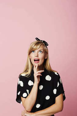 Portrait of young surprised woman looking up wearing polka dot dress