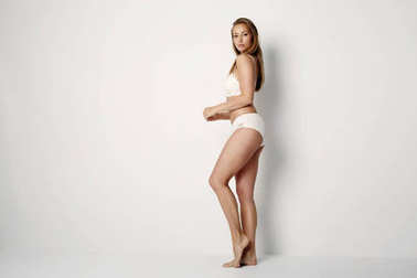 Young woman in white underwear posing at camera