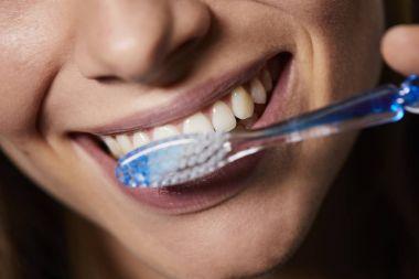 closeup view of woman brushing teeth