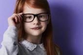 Zrzavá dívka úprava brýlí při pohledu na fotoaparát, portrét