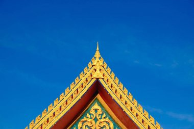Gold color roof of buddhist temple with blue sky background.
