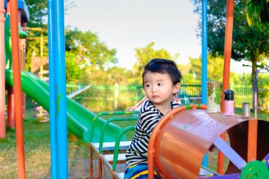 Young Asian boy play a iron train swinging at the playground und