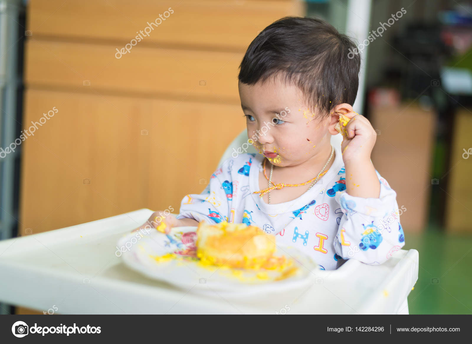 Asian kid eating birthday cake with cream on face Stock Photo